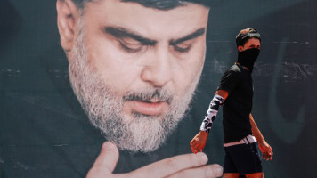 A youth walks in front of a large poster of Iraq's populist Shia cleric Moqtada Sadr, in Sadr City, east of the capital Baghdad, on 15 July 2021. [Getty]