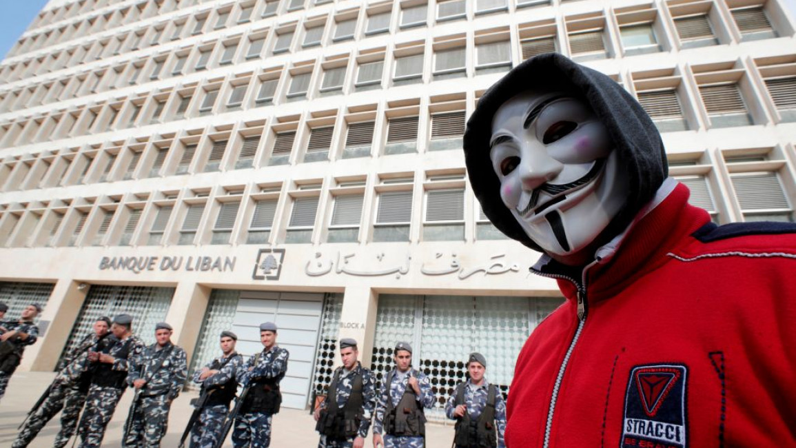 A demonstrator looks on as Lebanese policemen stand guard outside the Lebanese Central Bank in Beirut. [Getty]