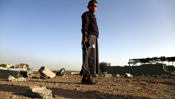 A Yemeni child holds missile shrapnel outside a factory after it destroyed in airstrikes carried out by warplanes of the Saudi-led coalition killing three civilians and injured six others on January 20, 2019 in Sana'a, Yemen. [Getty]