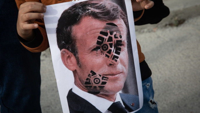 A boy holds a poster showing the portrait of French President Emmanuel Macron during a protest against him on 25 October 2020 in Istanbul, Turkey. [Getty]
