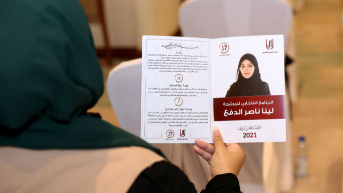 A woman holds a leaflet for the candidate for Qatars Shura council elections in the 17th constituency, Leena Nasser al-Dafa, during a campaign event in Doha