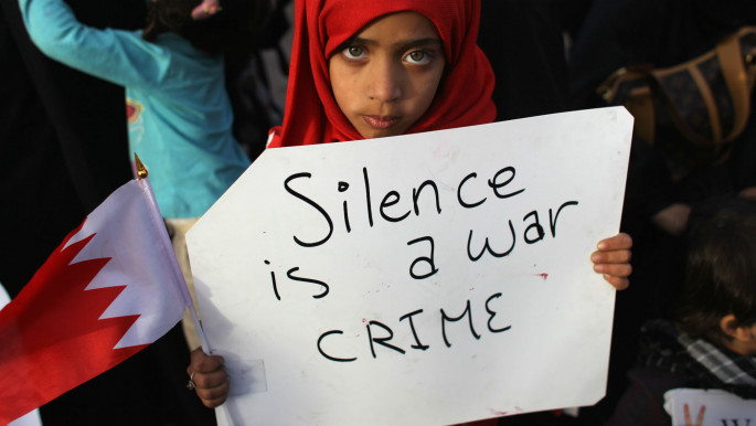 Young protester holds up a sign decrying international silence [Getty]