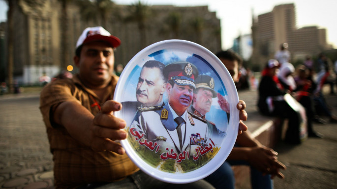 """Sisi supporter celebrates Sisi's presidential election win, holding image of Sisi, Nasser and Sadat with the subtitle """"Heroes of the Arab World"""" [Getty]"""
