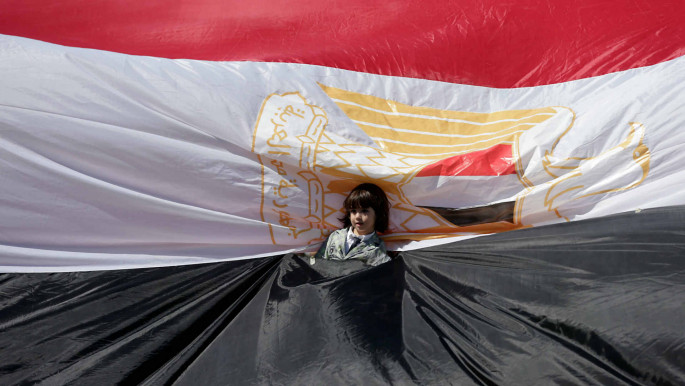 A young girl stands wrapped in an Egyptian flag as Palestinians gather in Gaza City to celebrate after rival Palestinian factions Hamas and Fatah reached an agreement [Getty]