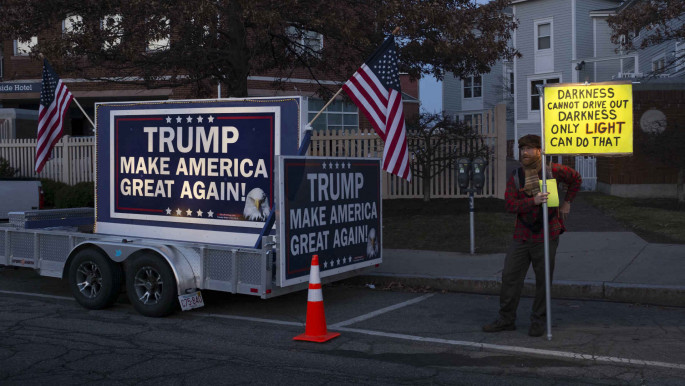A protester stands beside a pro-Trump billboard  Portsmouth, New Hampshire 2015 [Getty]