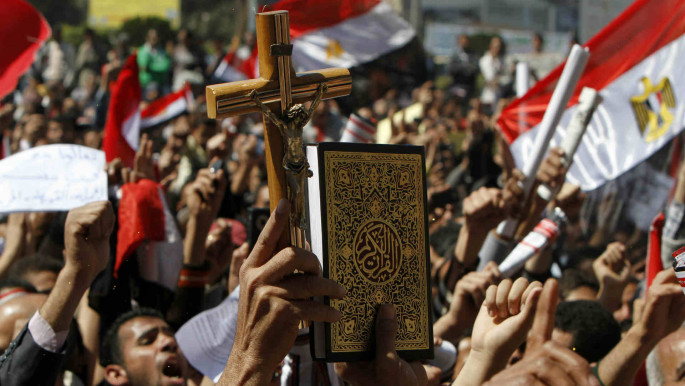 Protesters in Egypt's Tahrir Square hold up Qur'an and crucifix as sign of sectarian unity [Getty]