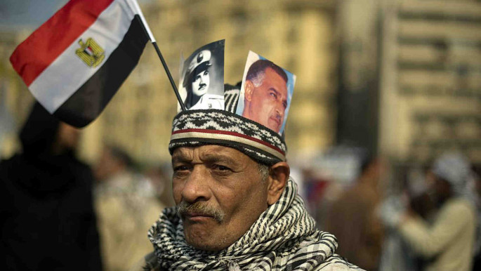 An anti-military rule protester wears a hat holding portraits of President Nasser December 2011